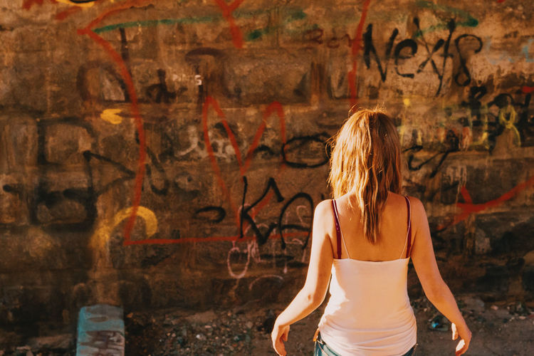 Rear View Of Woman Standing Against Graffiti Wall On Sunny Day