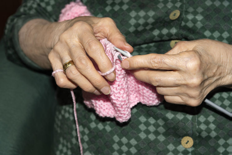 Midsection of senior woman knitting wool at home