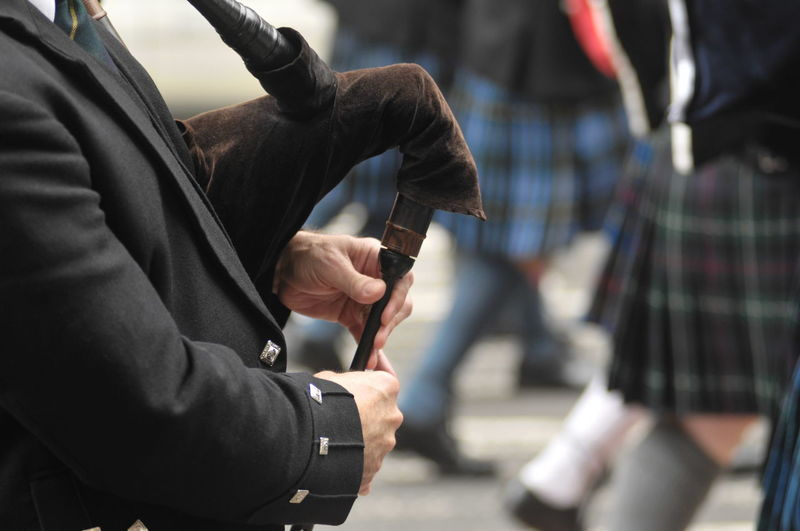 Midsection Of Street Musician Playing Bagpipe