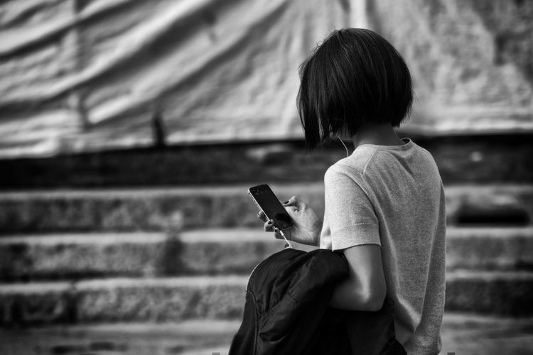 Black & White Black And White Brunette Girl  Casual Clothing Cell Cellphone Childhood Day Earphones Focus On Foreground Girl Headphones Outdoors Phone Rear View Short Hair Standing Street Street Photography Three Quarter Length Waist Up Woman
