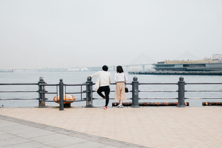 Rear view of couple standing by railing on pier against sky