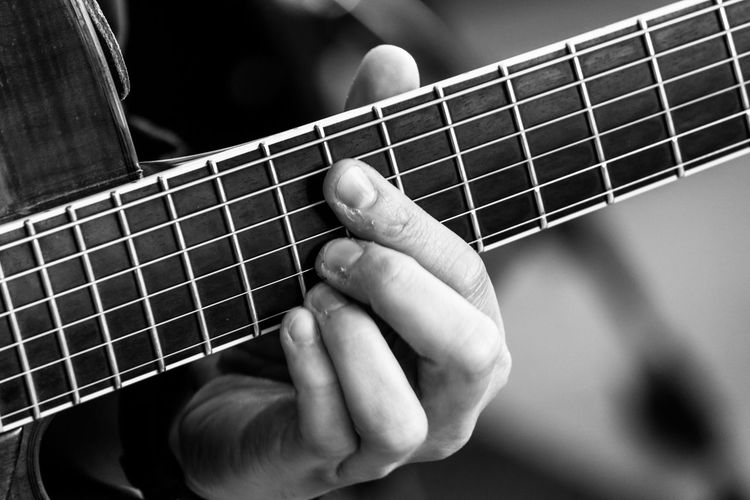 Arts Culture And Entertainment Classical Guitar Close-up Day Fretboard Guitar Human Body Part Human Finger Human Hand Indoors  Leisure Activity Lifestyles Music Musical Instrument Musical Instrument String Musician One Person People Playing Plucking An Instrument Real People