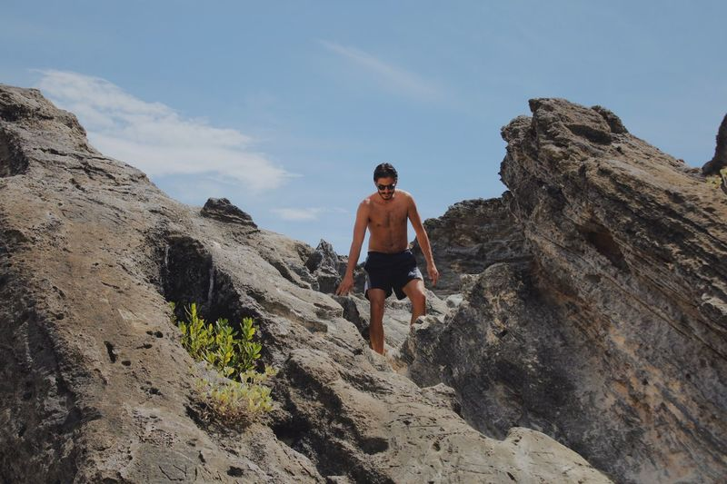 Low angle view of shirtless man standing on rock