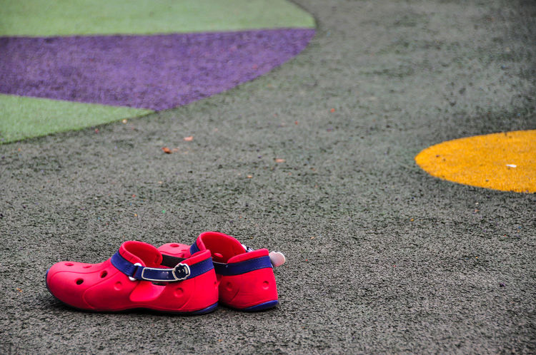 Red rubber shoe on imitating asphalt pavement. Asphalt Pavement Belt  Blue Childhood Circle Close-up Colorful Costume Day Gray Green Color Imitate Multi Colored No People Outdoors Pair Pattern Purple Red Red Color Rubber Shoes Sandal Shoe Ware Yellow Color