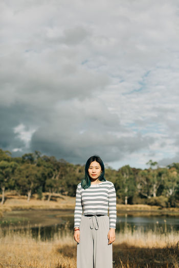 Cloud - Sky Standing One Person Sky Real People Front View Casual Clothing Nature Looking At Camera Portrait Three Quarter Length Land Lifestyles Young Adult Beauty In Nature Day Women Field Outdoors Hairstyle People Travel The Traveler - 2019 EyeEm Awards