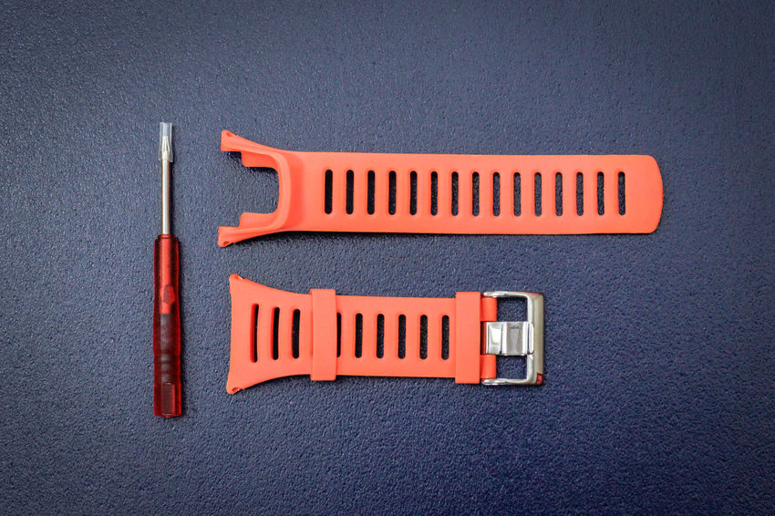 Orange watchband rubber skin & repairing tool kit for adjusting watchband on isolated blue background. Elégance Fashion Hour Orange Repairing Watch Band Wristwatch Belt  Blue Close-up Concept Design Display Gray High Angle View Indoors  No People Orange Color Red Rubber Still Life Studio Shot Tool Kit Watchband Wearables