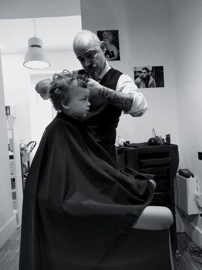 Barber cutting hair of boy at salon