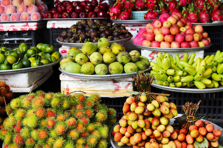An array of freshly grown tropical fruit at a market in Vietnam. Abundance Banana Choice Day Food Food And Drink For Sale Freshness Fruit Green Color Healthy Eating Landscape Large Group Of Objects Market Market Market Stall No People Outdoors Rambutan Retail  Small Business Tropical Tropical Climate Tropical Fruit Variation