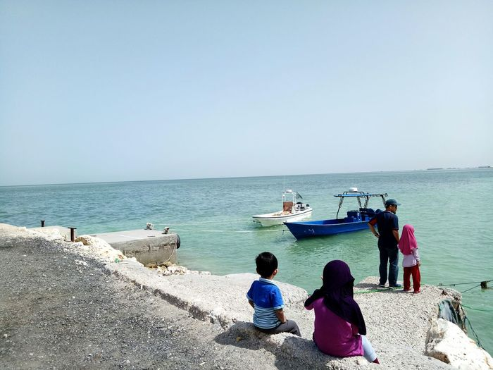 Rear View Of Father With Children On Shore Against Sky