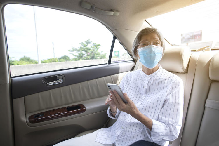 Woman using mobile phone while sitting in car