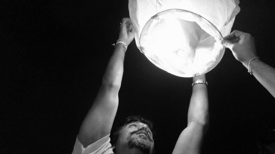 Close-up low angle view of man releasing paper lantern against clear sky at night