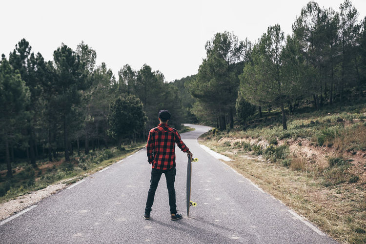 Rear View Of Man With Skateboard Standing On Road Amidst Trees Against Sky