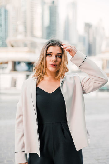 Young woman standing against wall in city