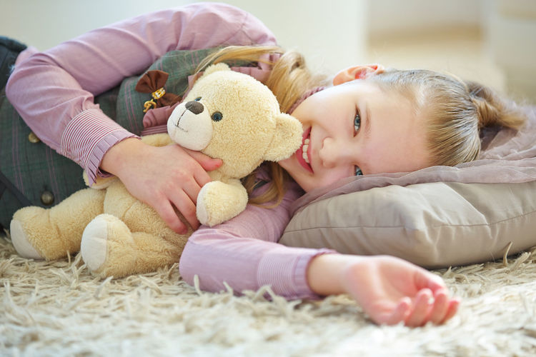Portrait of smiling girl lying on toy