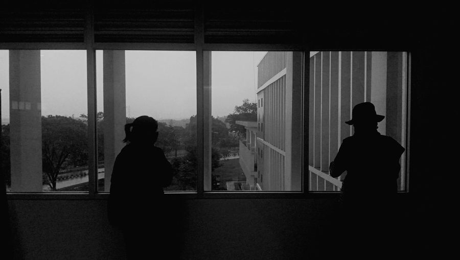 Rear view of silhouette two womans in physical distance standing by window