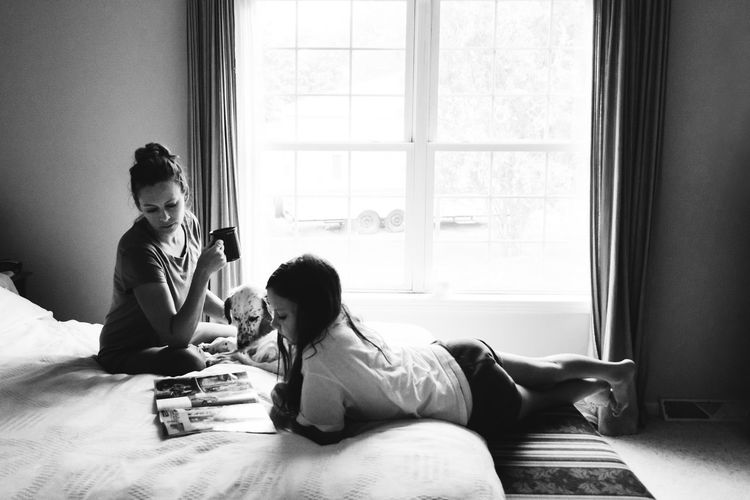 Mother And Daughter Reading Magazine On Bed At Home