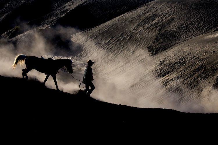 Silhouette man riding on mountain against sky