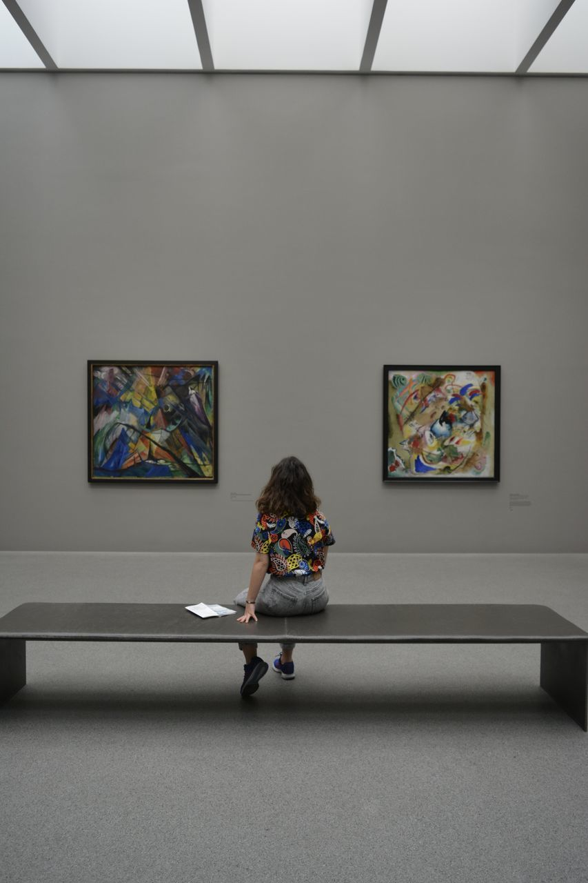 indoors, full length, one person, real people, lifestyles, art and craft, leisure activity, wall - building feature, museum, picture frame, sitting, frame, childhood, paintings, child, paint, creativity, casual clothing, innocence