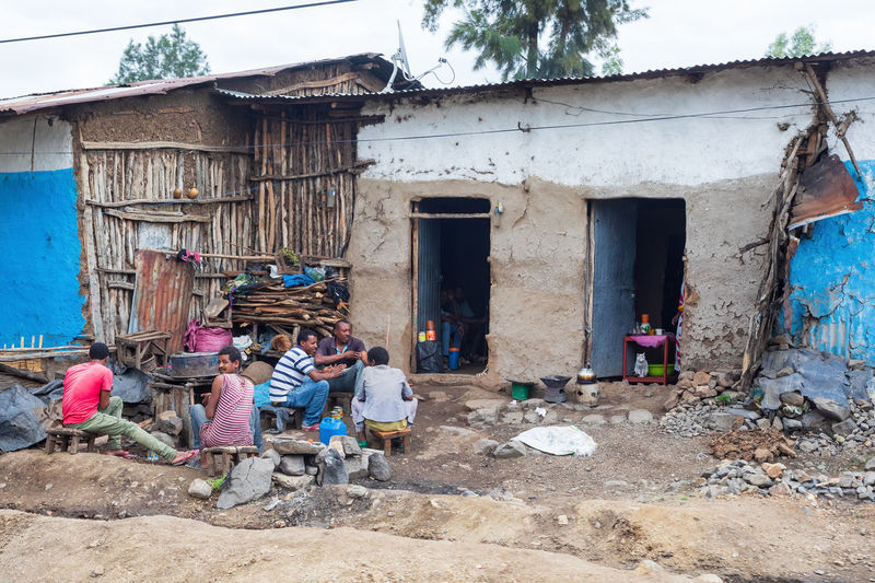 People working outside house in village