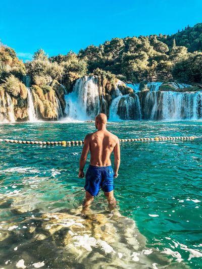 Full length of shirtless man standing on rocks against blue sky
