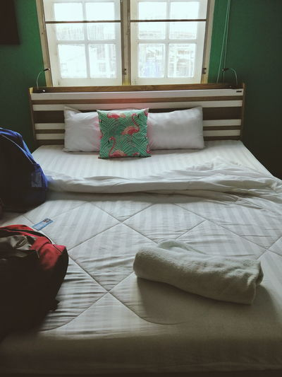 View of messy bed in bedroom