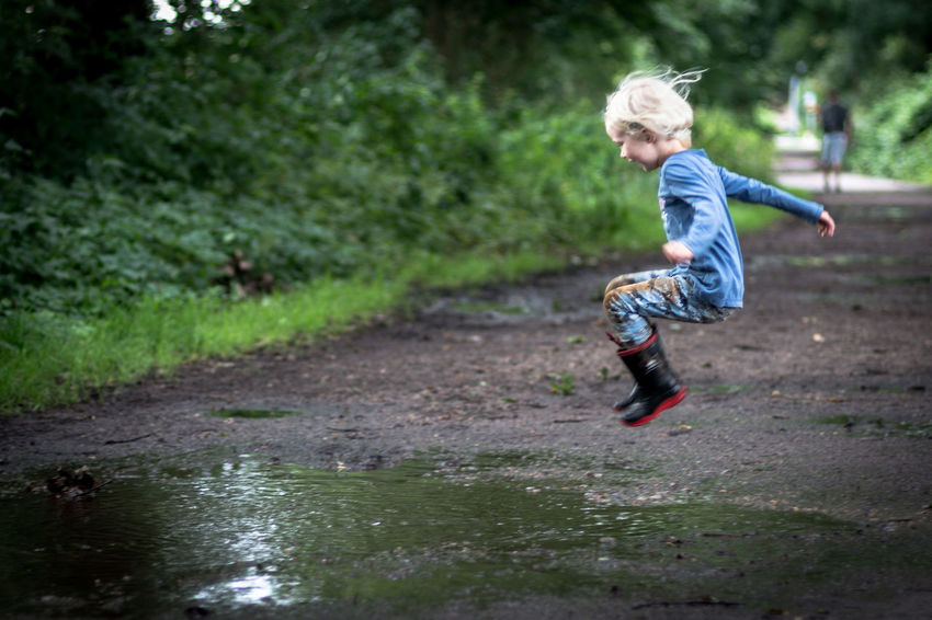 before landing 2 EyeEm Best Shots Fun Jump Kids Kids Being Kids Nature Pure Blond Hair Childhood Children Only Day Dirt Dirty Full Length Girl Jumping Kidsphotography Little Girl Muddy Nature One Person Outdoors Puddle Rubber Boots EyeEm Ready