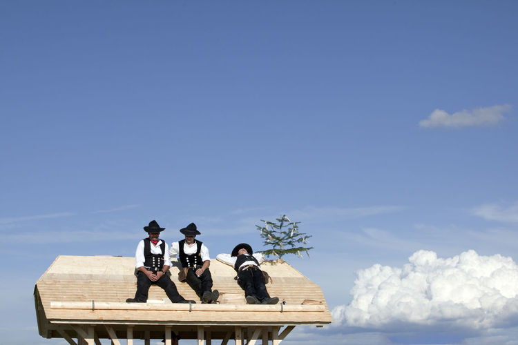 Traditional carpenters on rooftop Black Forest Blue Carpenter July showcase Cloud - Sky Costume Day Germany Lifestyles Low Angle View Nature Outdoors Relaxation Rooftop Sitting Sky Timber Tradition Tranquility Work