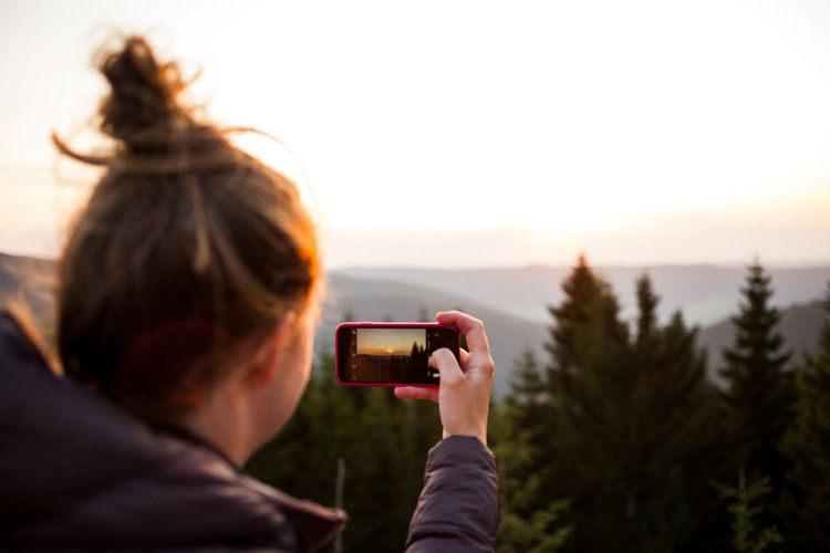 Rear view of woman photographing mountain during sunrise