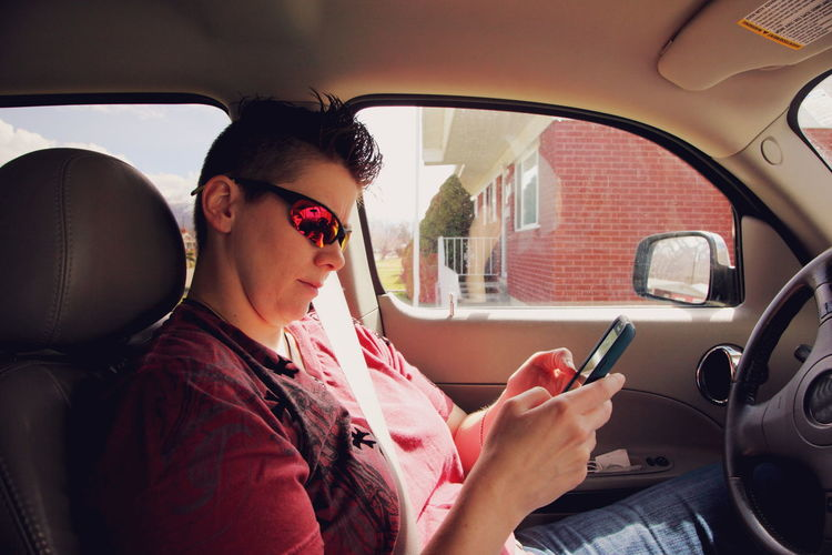 Lgbt Lesbian Queer Women Car Car Interior Holding Lesbian Mode Of Transport Person Phone Sitting Smartphone Sunglasses Technology Transportation Travel Vehicle Interior Wireless Technology Woman Young Women Mobile Conversations Text Messaging Using Phone