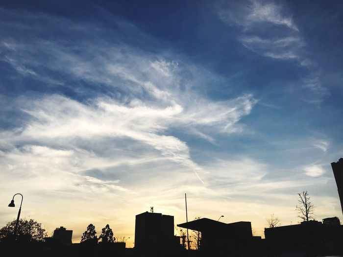 Low angle view of silhouette cityscape against sky