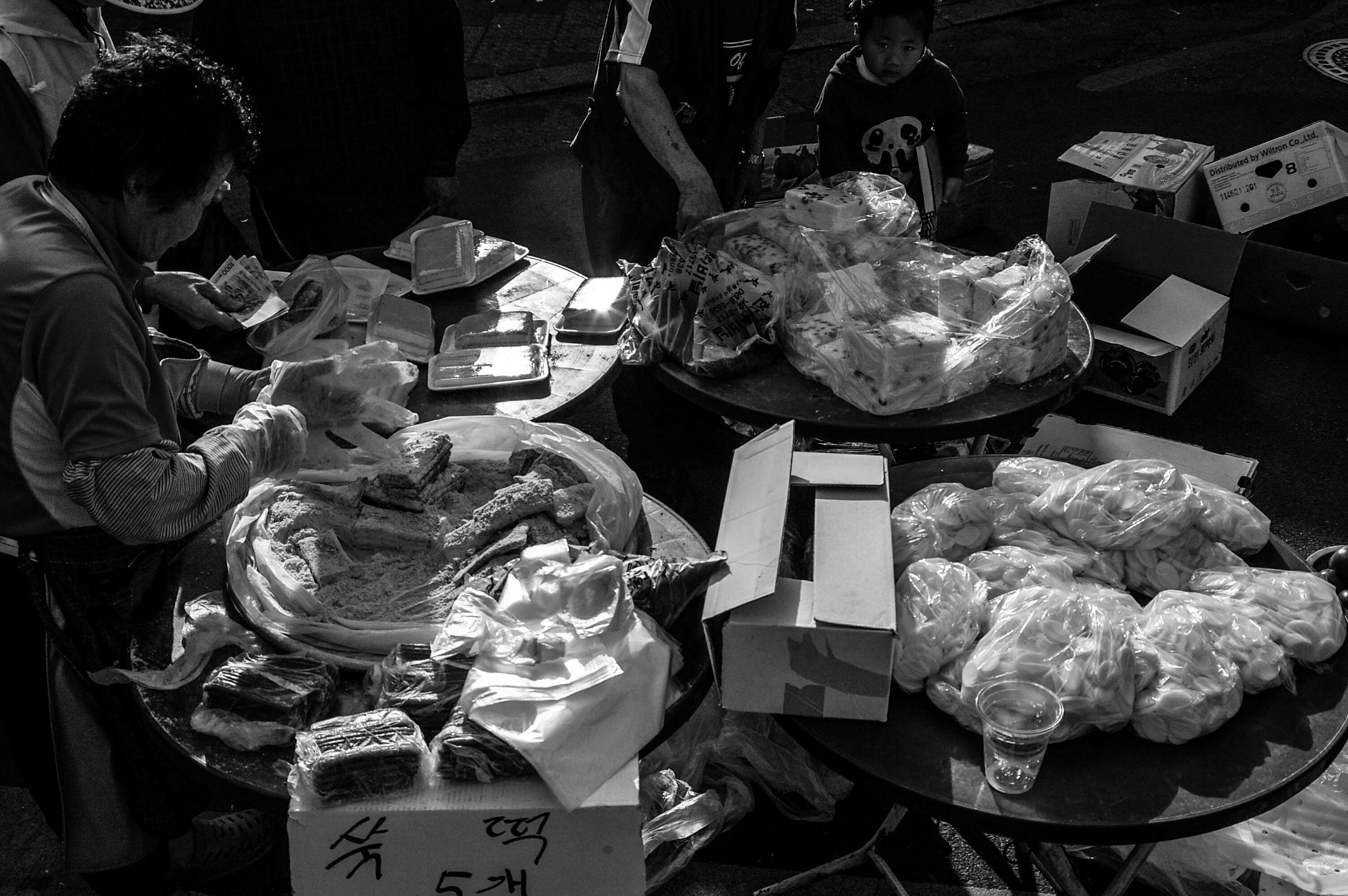 indoors, food and drink, food, freshness, retail, for sale, market, men, small business, holding, incidental people, high angle view, market stall, still life, working, occupation, preparation, human representation