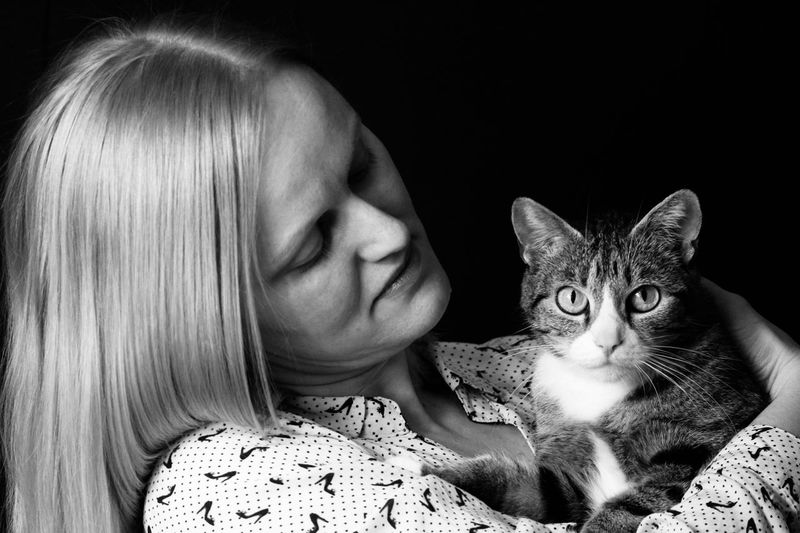 Close-up of mid adult woman holding cat against black background