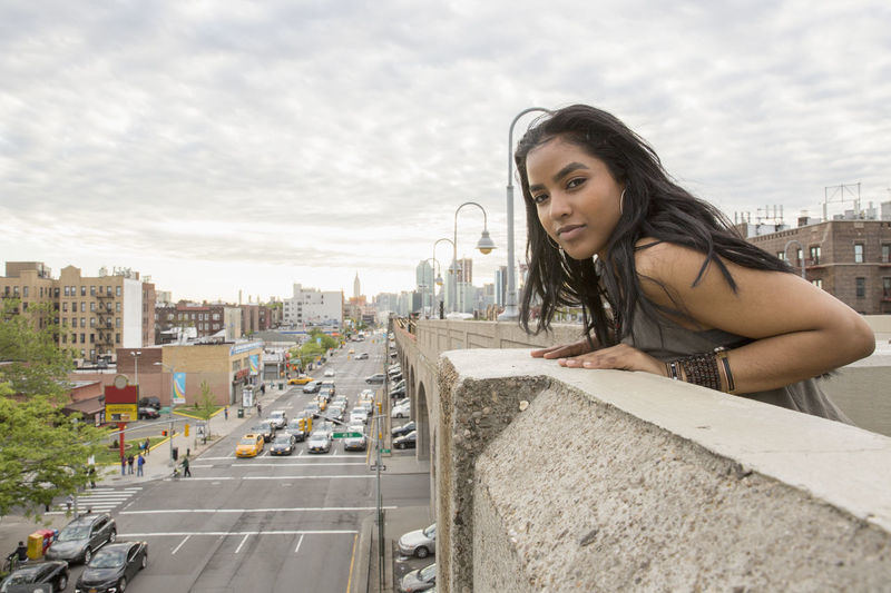 Side view of young woman looking at cityscape