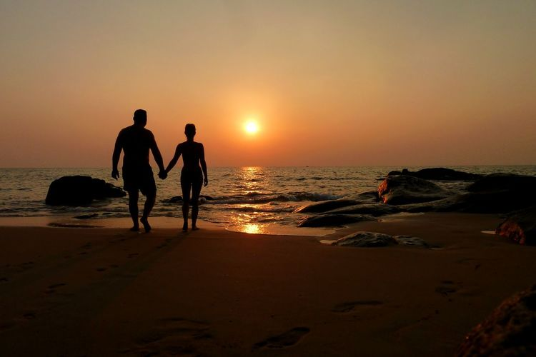 Rear view of silhouette man and woman holding hands while walking on shore during sunset