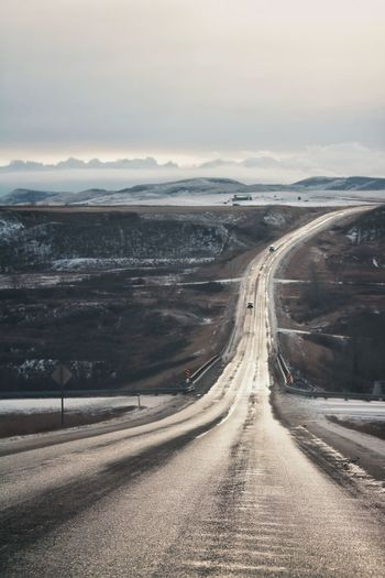 Road passing through prairie landscape towards mountains in winter
