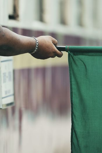 Cropped hand of train dispatcher holding green flag