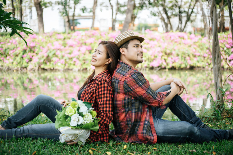 Adult Boyfriend Casual Clothing Couple - Relationship Emotion Full Length Girlfriend Grass Hat Heterosexual Couple Love Men Nature Outdoors Plant Positive Emotion Sitting Smiling Togetherness Two People Young Adult Young Couple Young Men Young Women