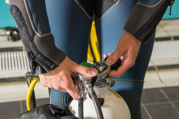 Midsection of woman opening scuba diving gas cylinder