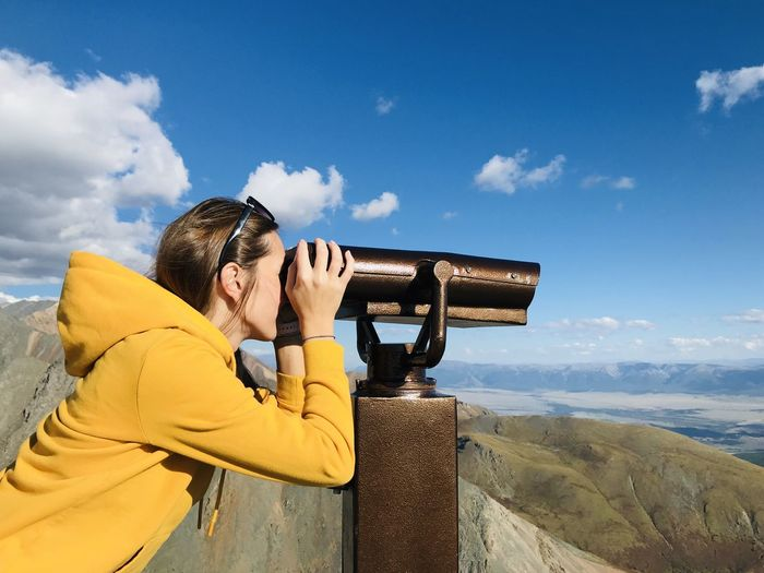 Side view of woman looking though binoculars against sky