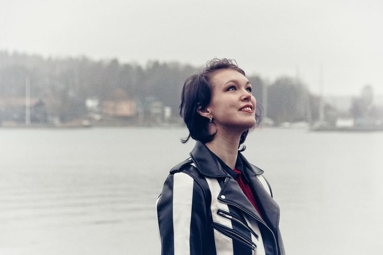Close-up of smiling young woman looking away while standing against lake