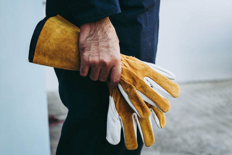 Close-up of man holding gloves at industry