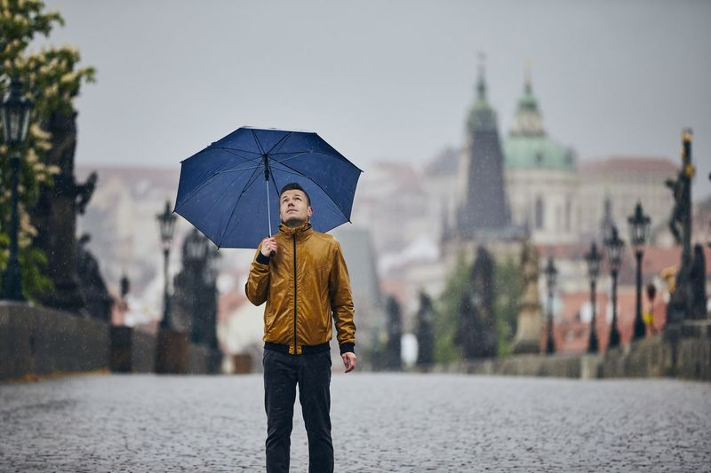 Man standing on wet umbrella in city during rainy season