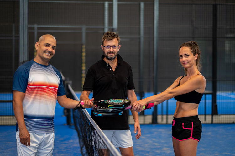 Portrait of smiling sportsman's posing indoor on padel court with rackets and balls