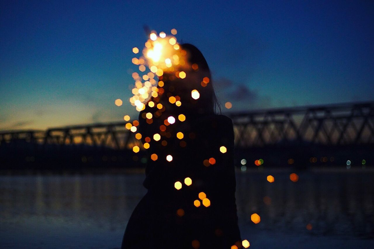 Digital Composite Image Of Silhouette Woman With Illuminated Lights By Lake At Dusk