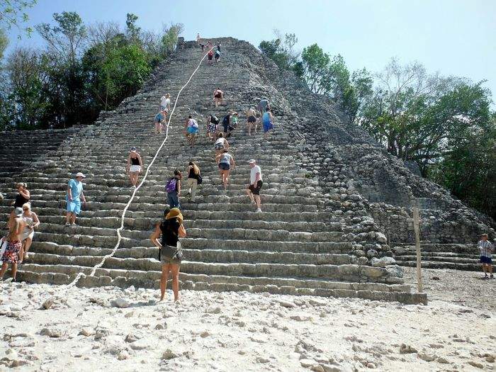 Tourists climbing stone steps of xaibe pyramid against sky