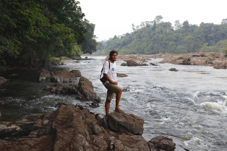 Man standing on rocks by river