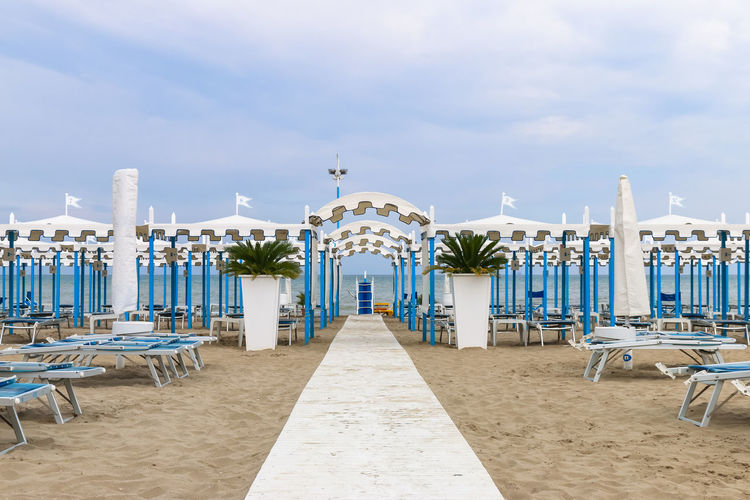 Empty beach, Italy, Riccione Canopy Deck Chair Footpath Italy. Riccione Rimini Vacations Adriatic Sea Beach Blue Cloud - Sky Day Empty Italy Luxury No People Outdoors Potted Plant Resort Riccione Sand Sea Sky Walkway Water White
