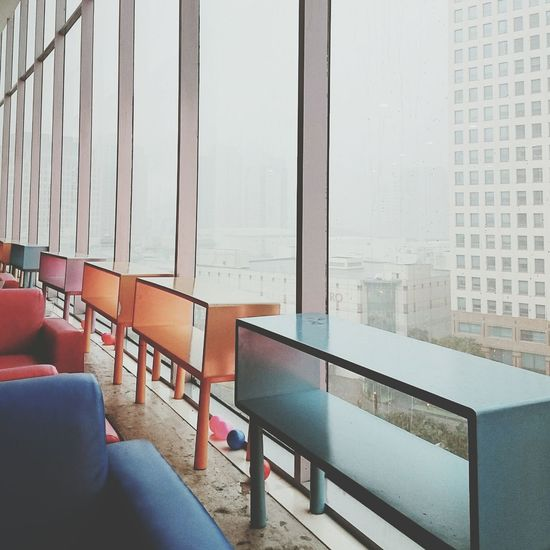 Tables And Armchairs On Floor In Building During Foggy Weather