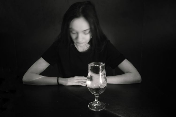 Close-up of woman holding drink in glass on table