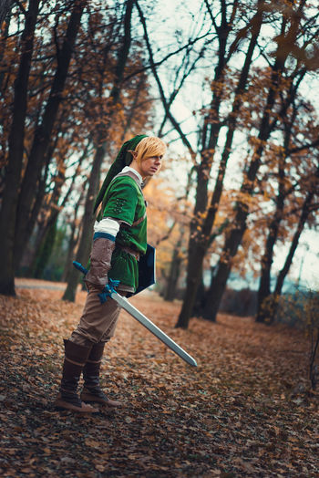 Side View Of Young Man Wearing Cosplay Costume While Standing In Forest During Autumn